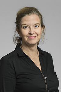 Porträttbild av Pia Skott med neutral bakgrund.
