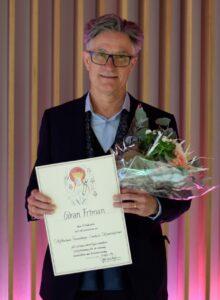 Göran Friman i Kostym med diplom och blommor i famnen